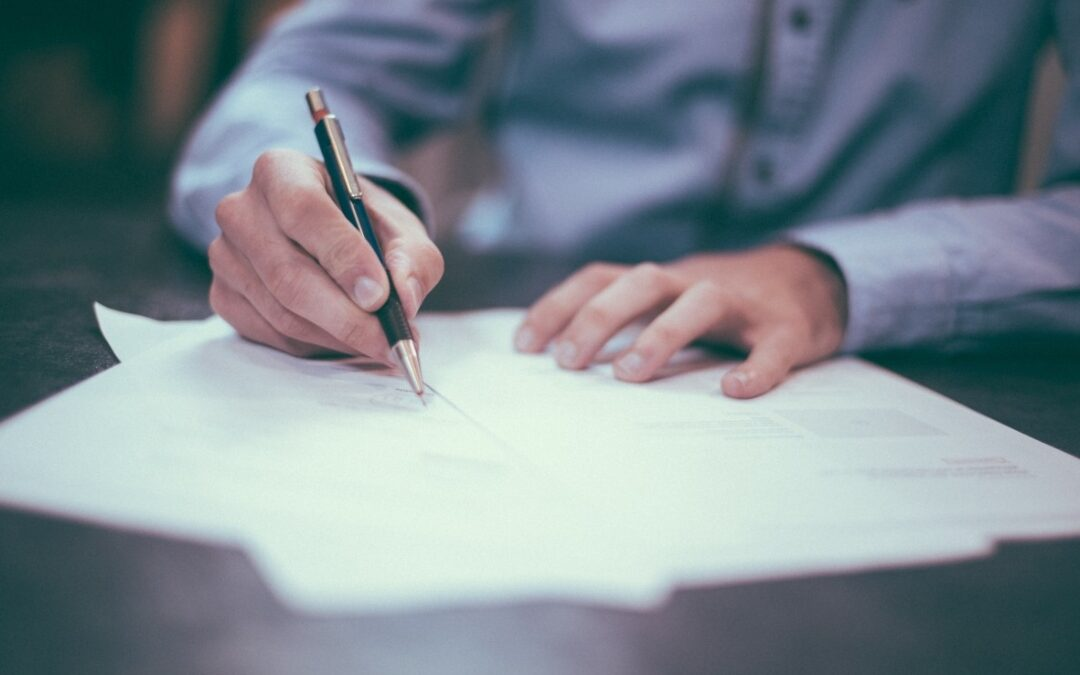 Na zdjęciu widać tors i ramiona mężczyzny w niebieskiej koszuli, który siedzi przy stole i pisze.