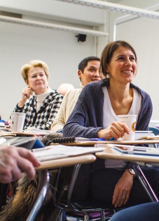 Na zdjęciu widać trzy osoby w różnym wieku, które siedzą przy stolikach z rozłożonymi książkami i uczestniczą w szkoleniu. Wyglądają na zainteresowane. Uśmiechają się.