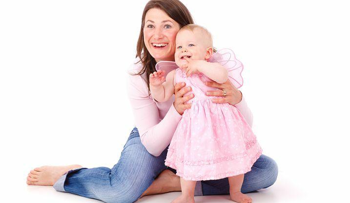 Na zdjęciu widać kobietę siedzącą na podłodze i trzymającą około roczną dziewczynkę w różowej sukience. Dziewczynka próbuje samodzielnie stać. Obie patrzą w swoją prawą stronę i się uśmiechają.