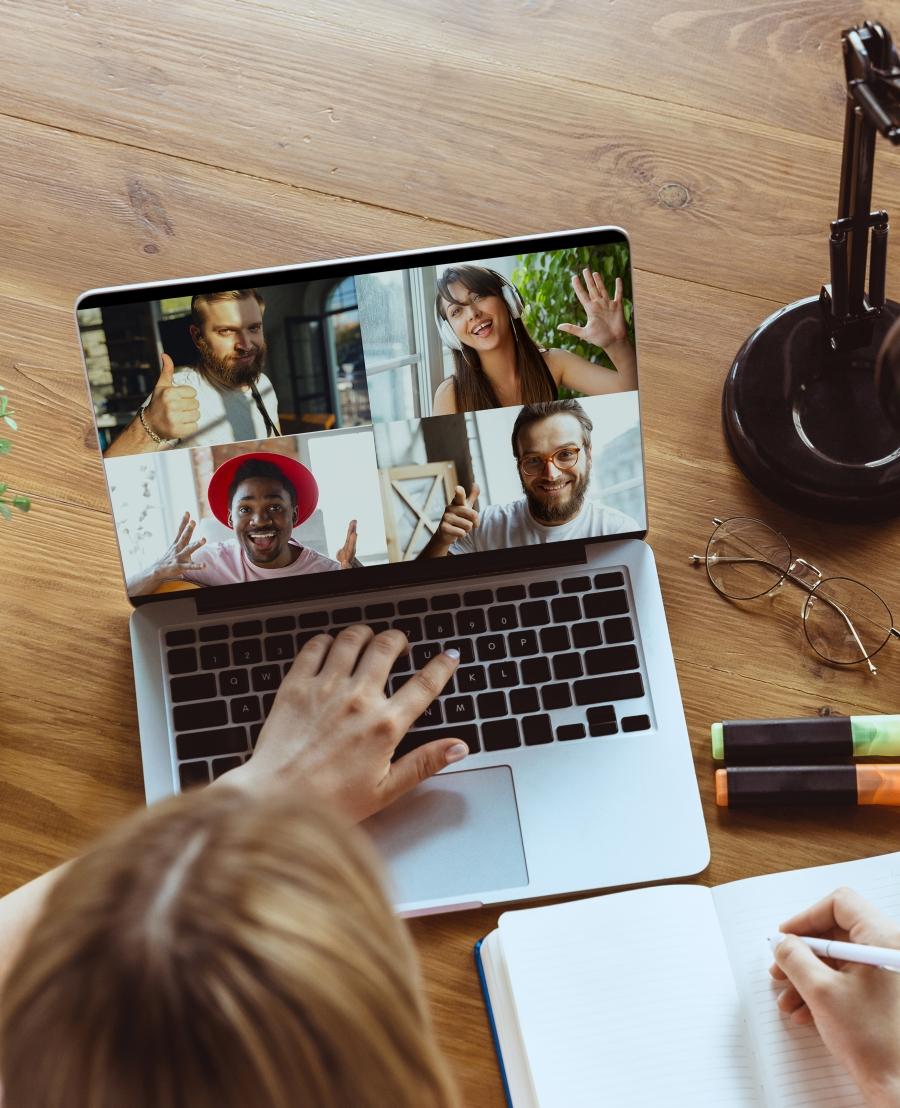 Na zdjęciu ktoś uczestniczy w spotkaniu online z czterema innymi osobami. Na biurku stoi otwarty laptop, obok okulary, lampka i flamastry. Widać dłoń kobiety na klawiaturze, a na ekranie zdjęcia czterech uśmiechniętych osób.