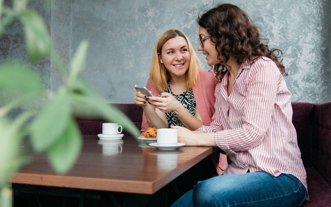 Na zdjęciu dwie młode kobiety siedzą przy stoliku w kawiarni i rozmawiają uśmiechając się do siebie. Jedna z nich trzyma telefon. Na stoliku znajdują się dwie filiżanki kawy i kawałek ciasta.