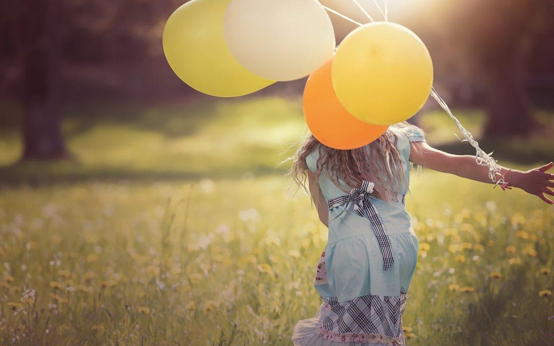 Jest słoneczny, letni dzień. Młoda dziewczyna zwrócona tyłem idzie w letniej sukience przez kwitnącą łąkę. Ma długie, blond włosy. Do prawej ręki ma przywiązany pęk Żółtych balonów.