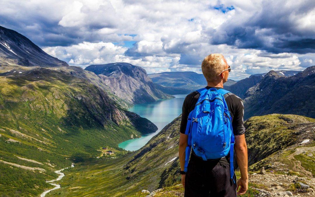 Młody mężczyzna z niebieskim plecakiem, w okularach przeciwsłonecznych stoi na wzgórzu i zastanawia się, w którą stronę pójść